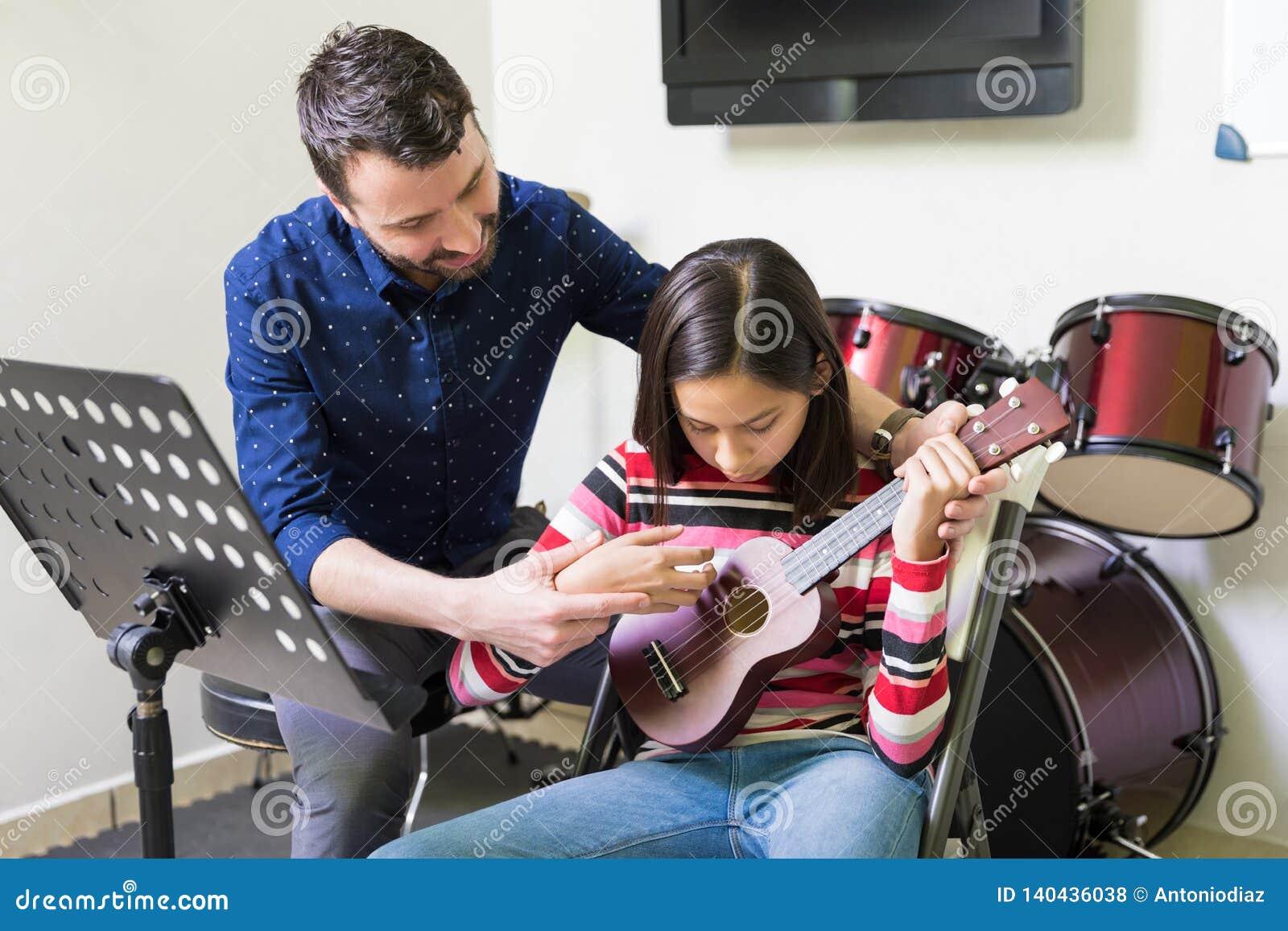 Entraîneur Assisting Teen Student en jouant l ukulélé