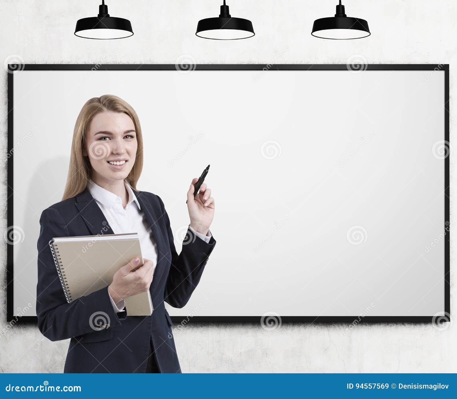 Entraîneur blond d affaires avec le marqueur, tableau blanc vide