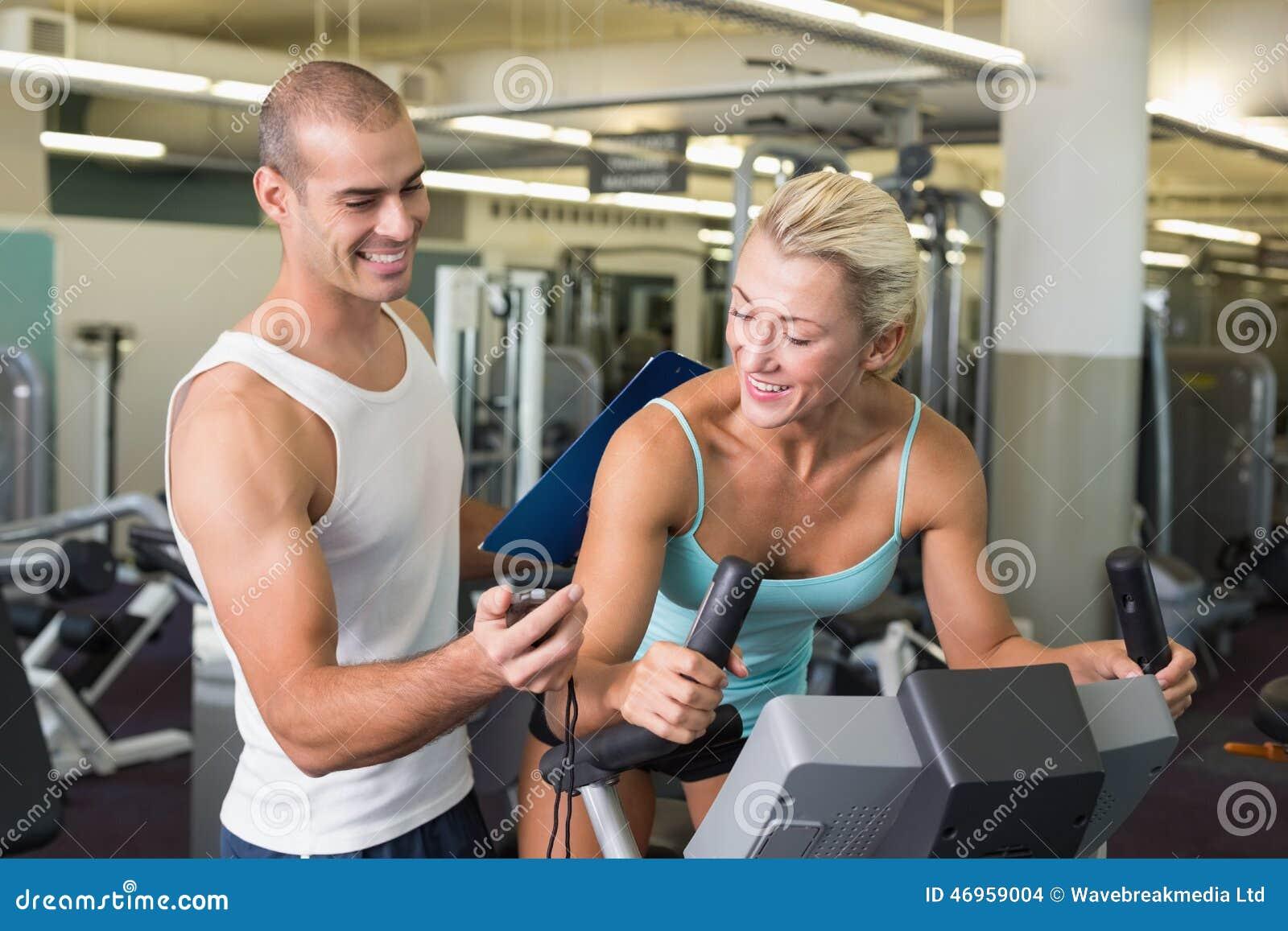 Entraîneur chronométrant son client sur le vélo d exercice au gymnase