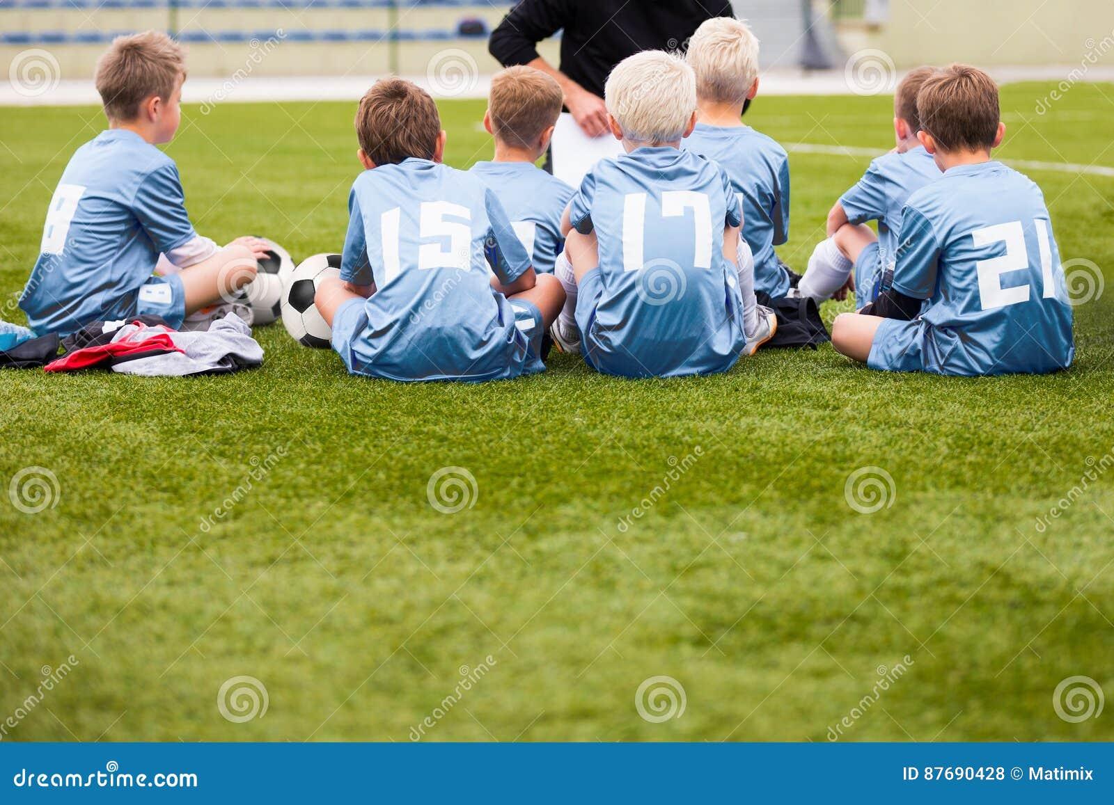 Entraîneur donnant de jeunes instructions d équipe de football Le football Team With Coach de la jeunesse