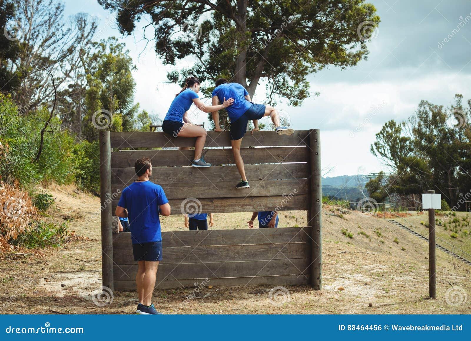 Entraîneur féminin aidant l homme convenable pour s élever au-dessus du mur en bois pendant le parcours du combattant