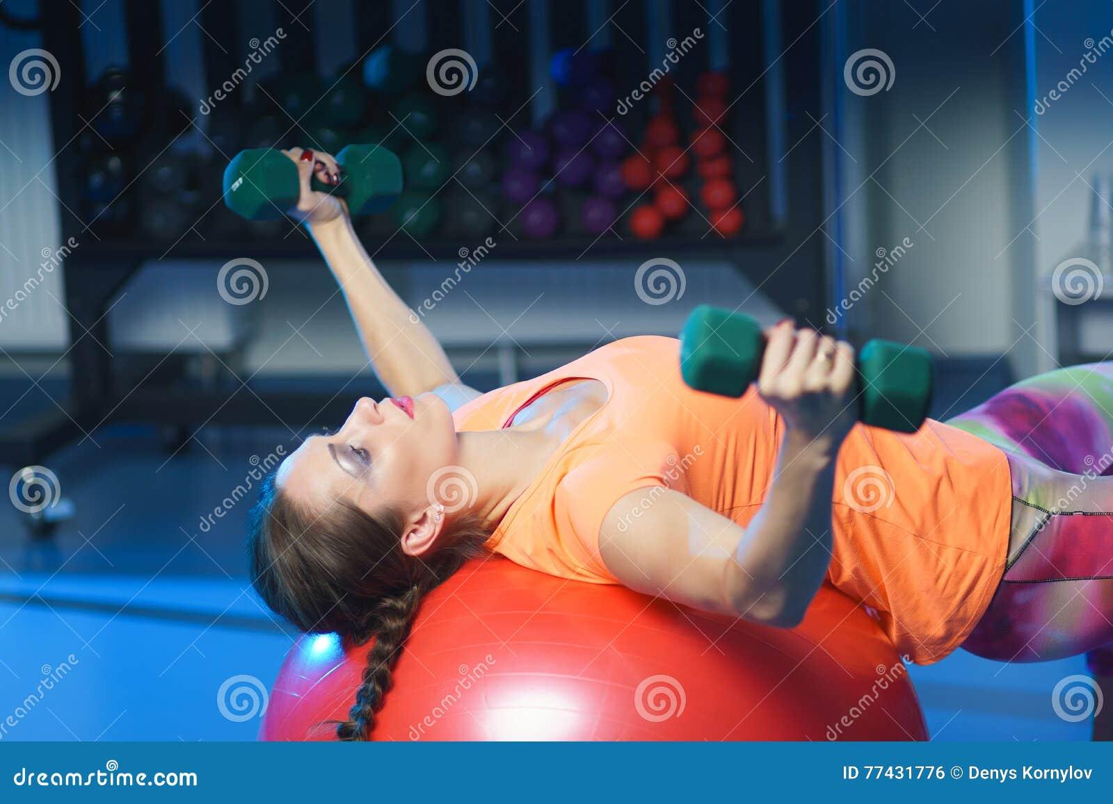 Entraîneur musculaire attirant puissant W de forme physique de femme orking