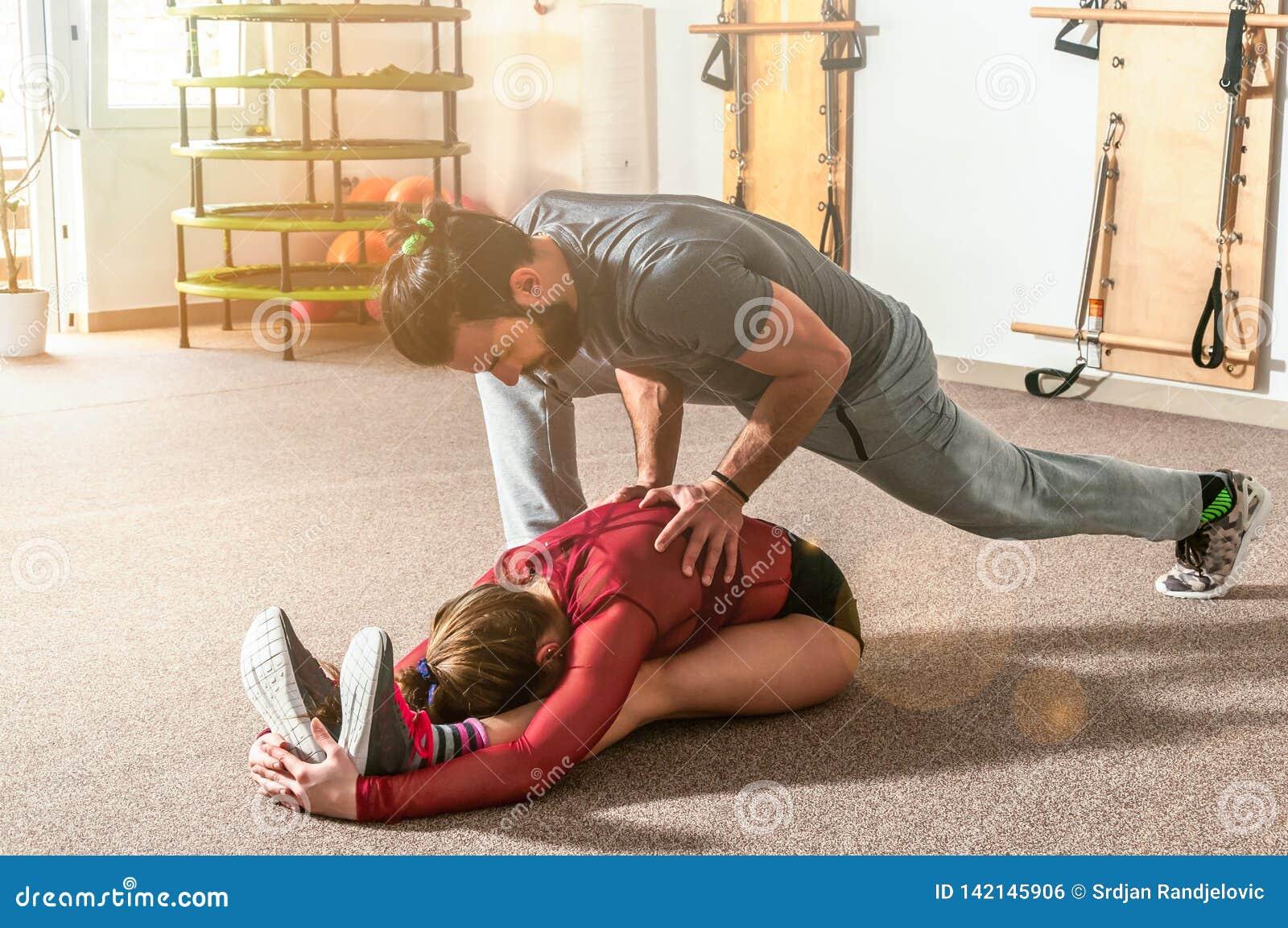 Entraîneur personnel masculin de yoga beau avec une barbe aidant la jeune fille de forme physique à étirer ses muscles après séan