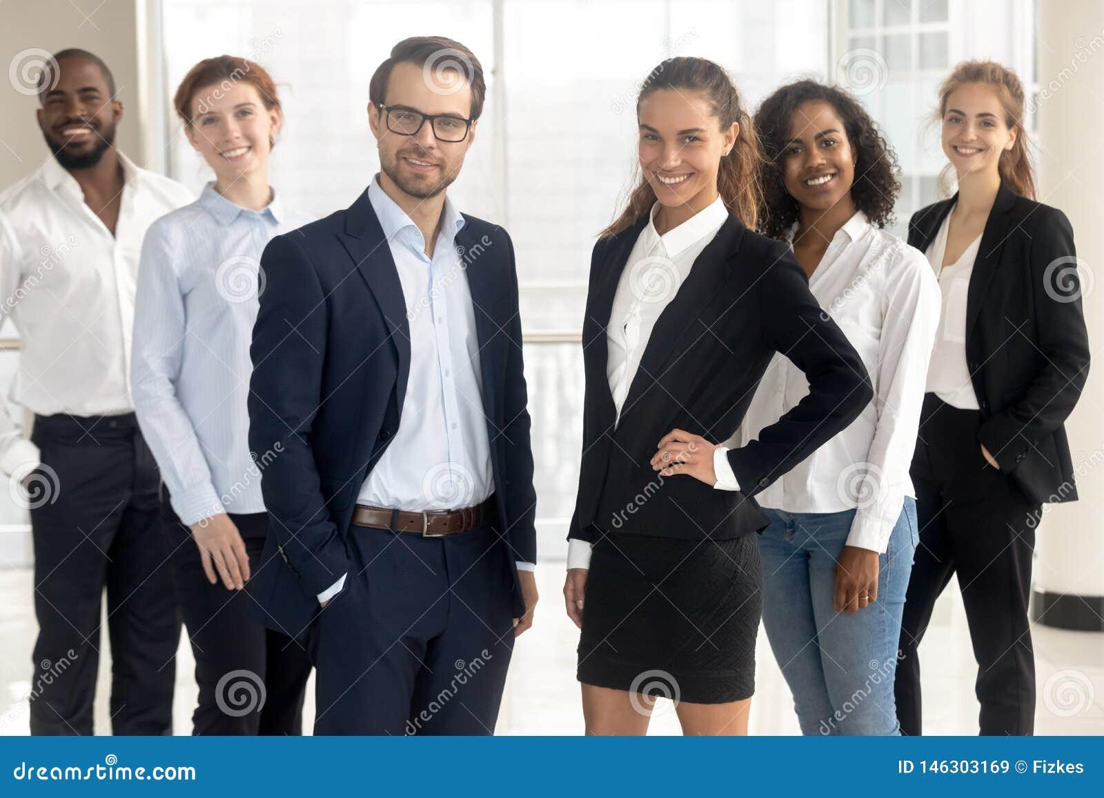 Entraîneurs professionnels de sourire de chefs regardant la caméra avec des hommes d affaires des employés