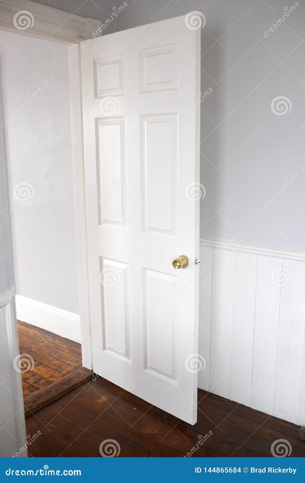 Entrada branca aberta com assoalhos de madeira