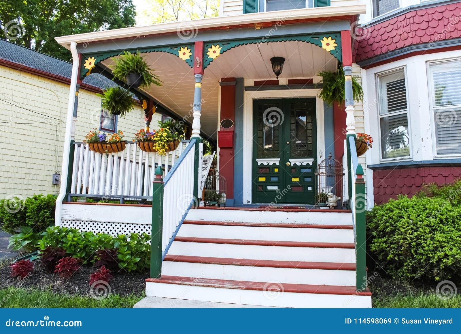 Entrada da casa ornamentado velha do estilo do victorian do pão-de-espécie decorada para o verão com flores e decoração do patama
