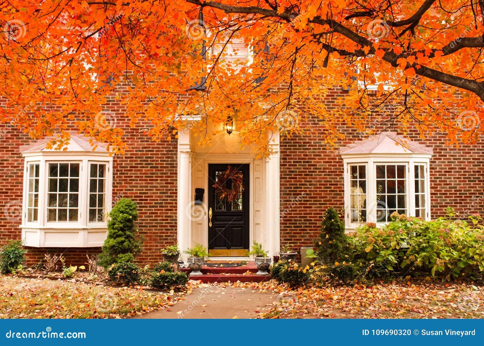 Entrada de la casa del ladrillo rojo con la guirnalda estacional en puerta y pórtico y ventanas saledizas el día del otoño con la