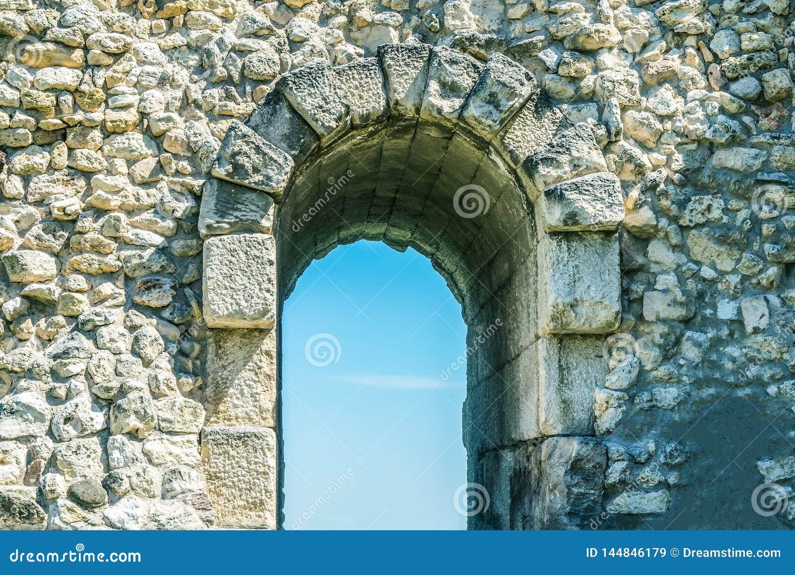 Entrada de la entrada en la pared de piedra, arco para la entrada y salida en las ruinas de la ciudad vieja
