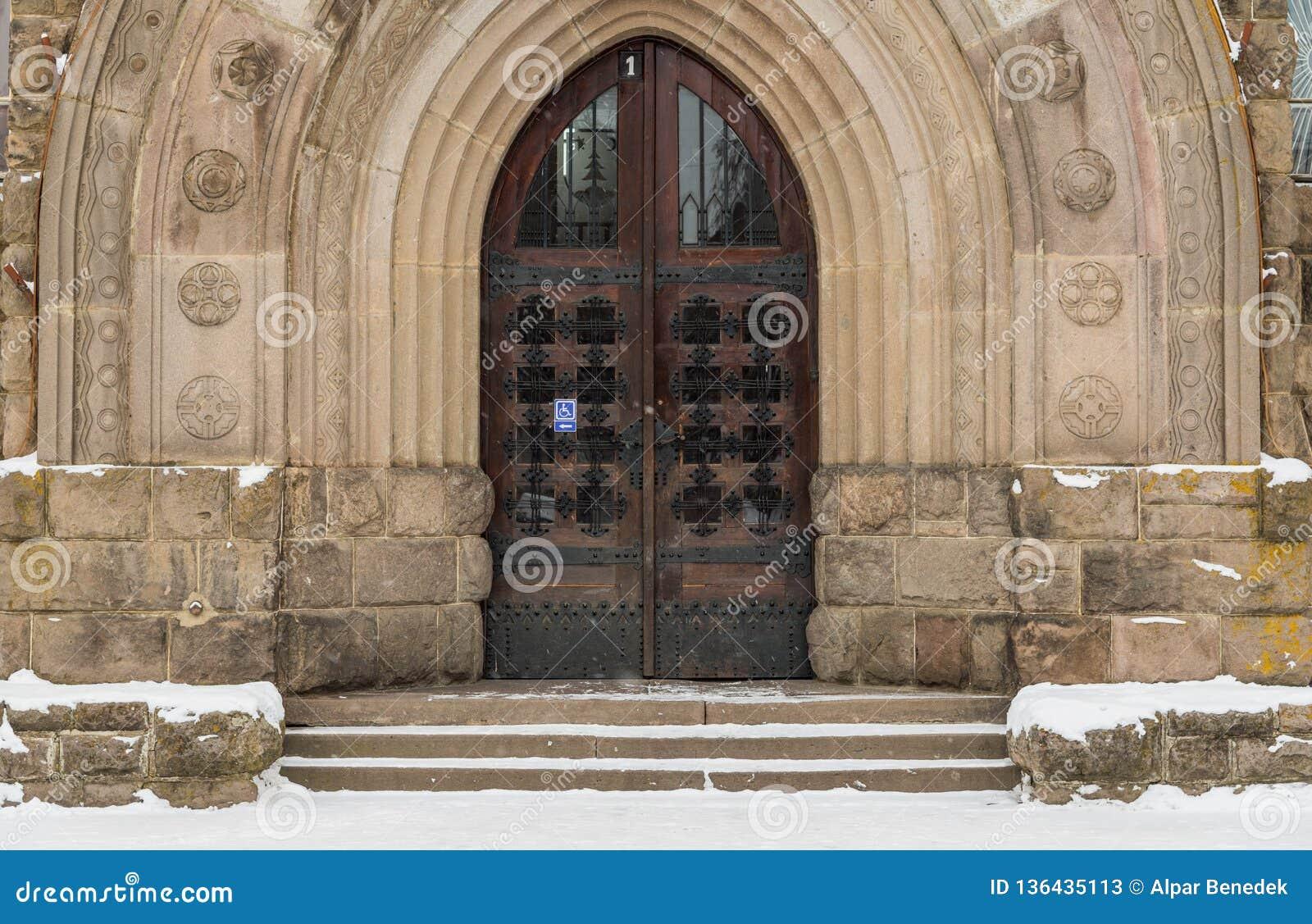 Entrada gótica de la puerta del roble en la institución pública en Transilvania