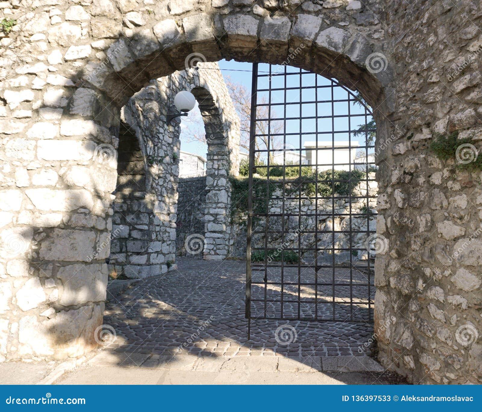 Entrada velha antiga da pedra do castelo com porta do ferro