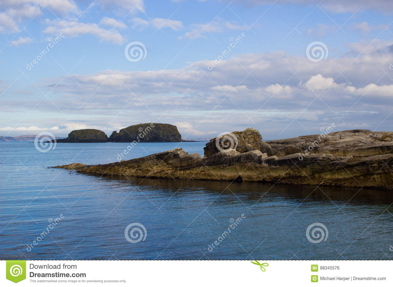 The entrance to Ballintoy harbor on the North Antrim Coast of Northern Ireland with its stone built boathouse on a day in spring
