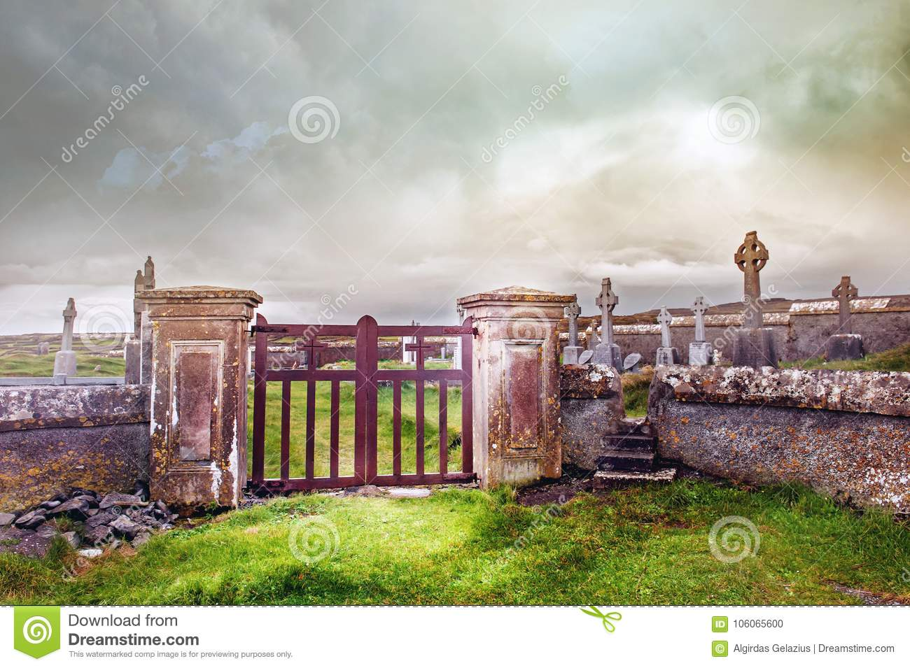 Entrance to the cemetery with metal gates and concrete fence