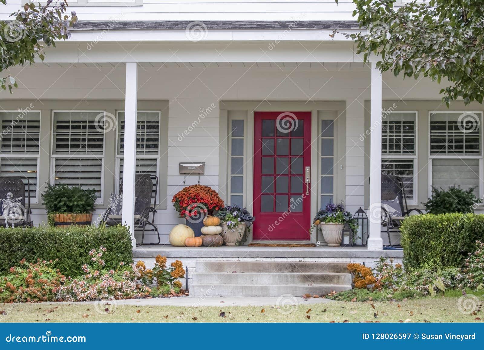 Entrata e portico alla casa graziosa con le decorazioni di Halloween e di autunno e foglie di caduta che soffiano nel vento - app