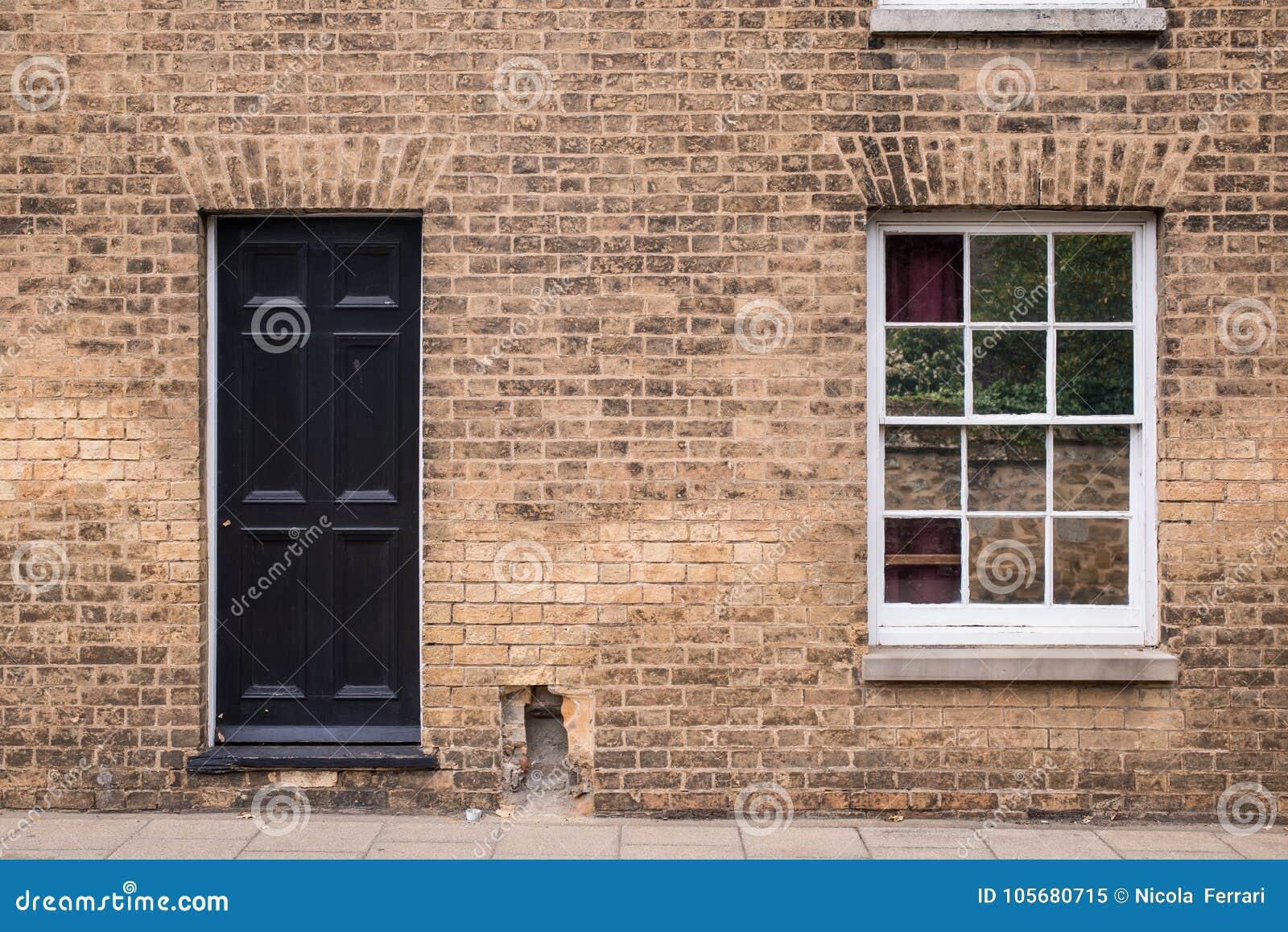 Entrata principale nera su un muro di mattoni ristabilito - Entrata di casa ...