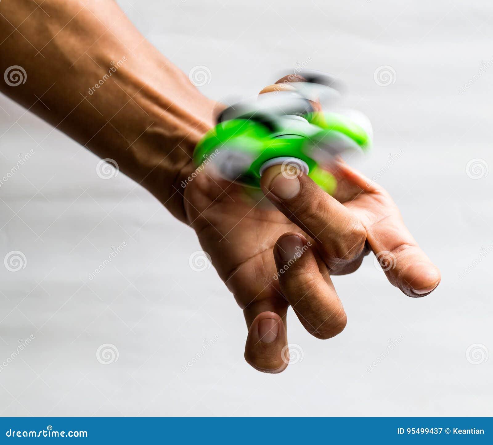 Entrega a rotação do verde do girador no dedo