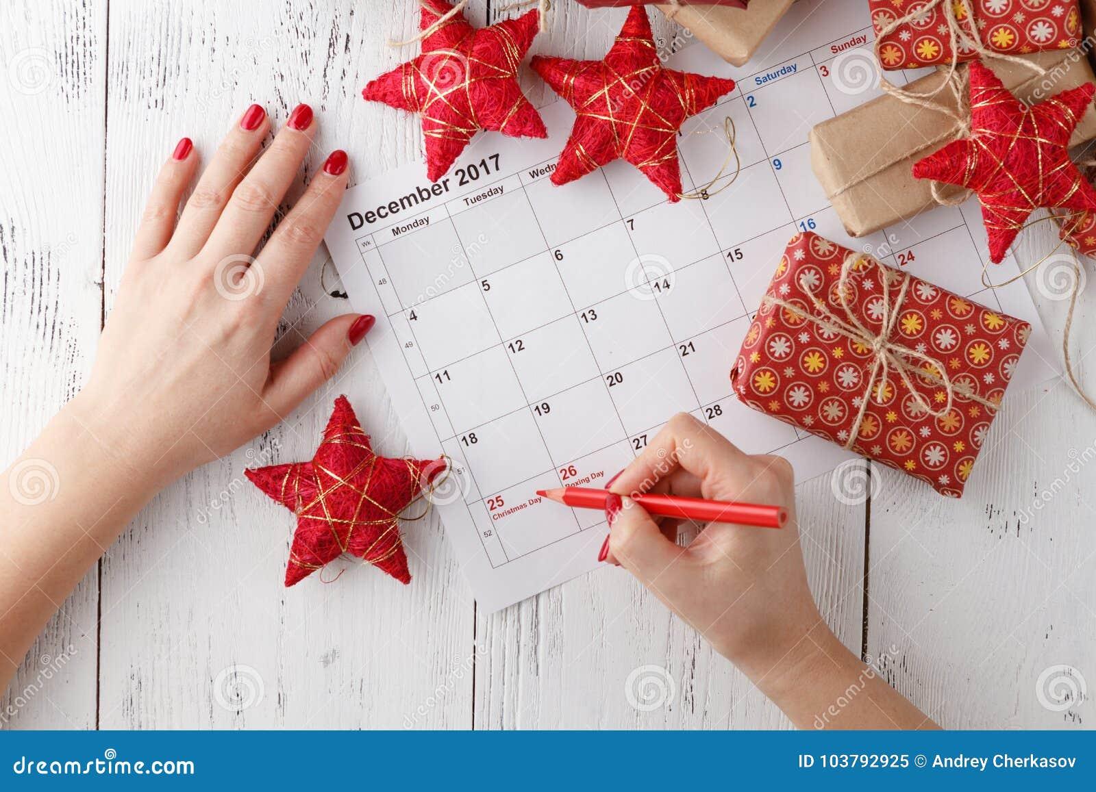 Entregue apontar o 25 de dezembro em um calendário cercado por ornamento do Natal