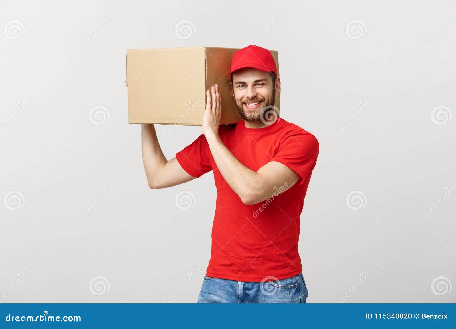 Entregue el concepto: Hombre de entrega hermoso caucásico joven que sostiene una caja en hombro Aislado sobre fondo gris