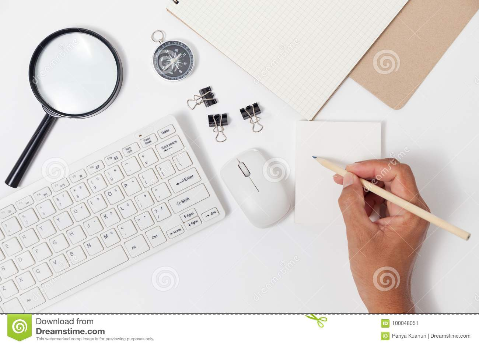 Entregue a escrita do lápis do uso em objetos da nota e do negócio do Livro Branco