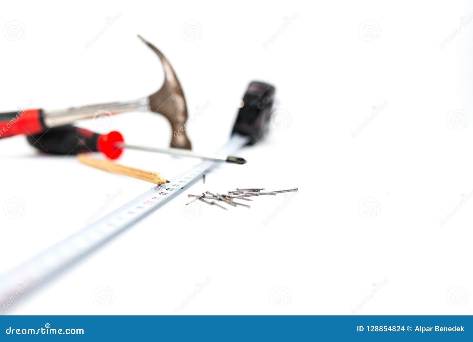 Entregue ferramentas no fundo, no martelo, na chave de fenda, na régua, no lápis e nos pregos brancos, profundidade de campo rasa