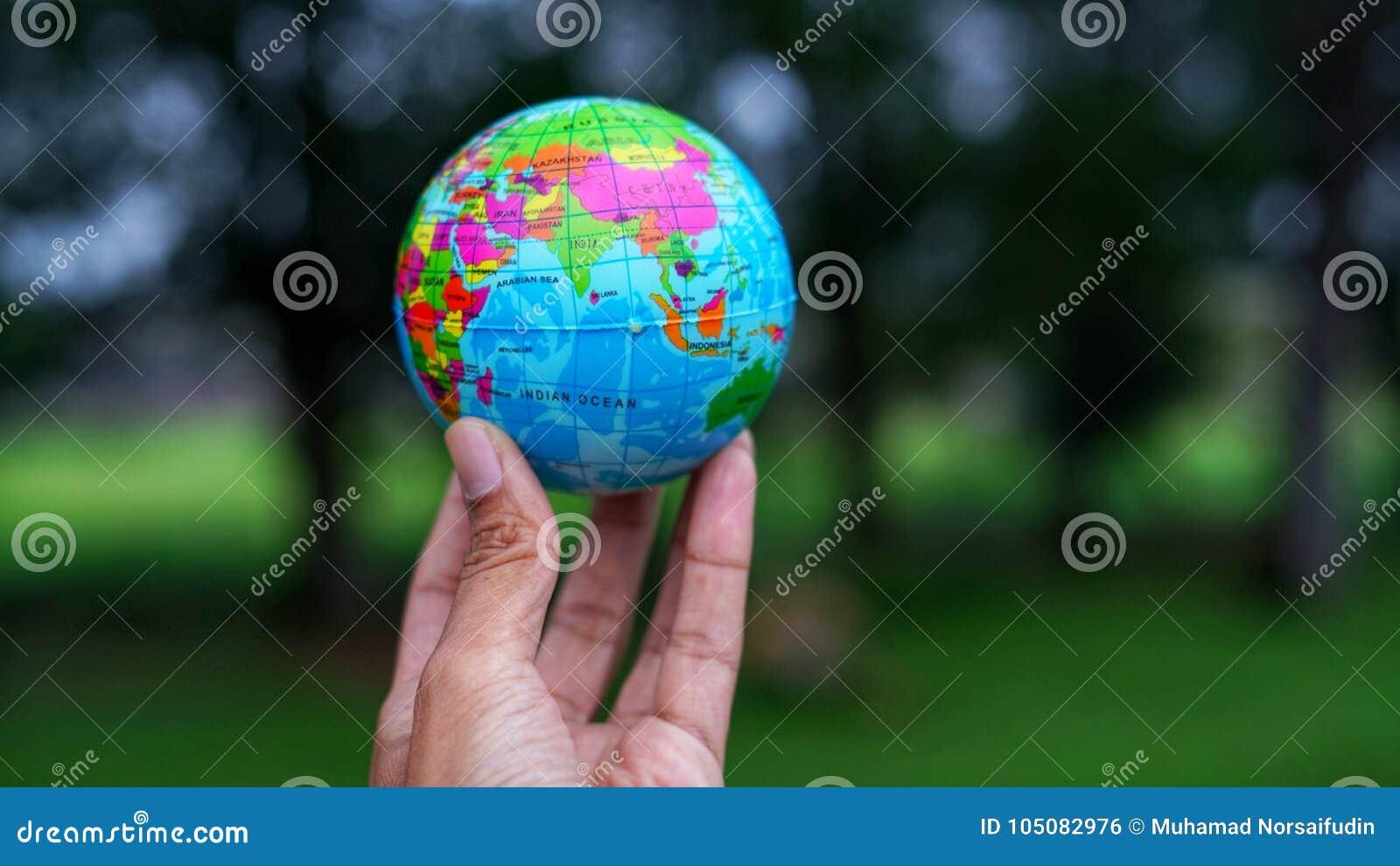 Entregue guardar a bola do globo do mundo com fundo do borrão