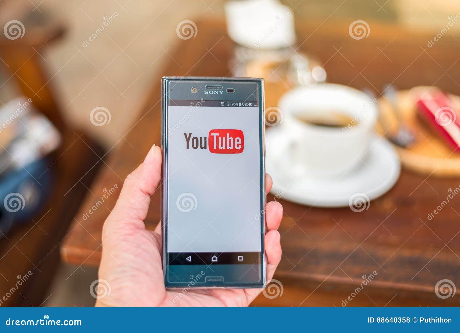 Entregue guardar o telefone celular com logotipo de youtube na download entregue guardar o telefone celular com logotipo de youtube na cafetaria foto de stock editorial ccuart Choice Image