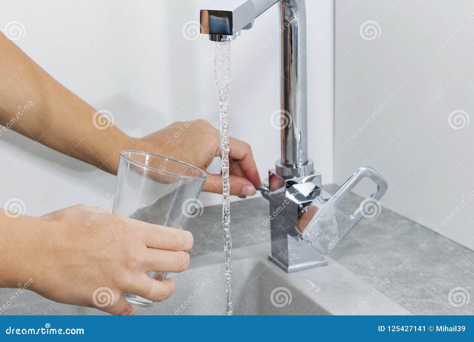 Entregue manter um vidro da água derramado do torneira da cozinha