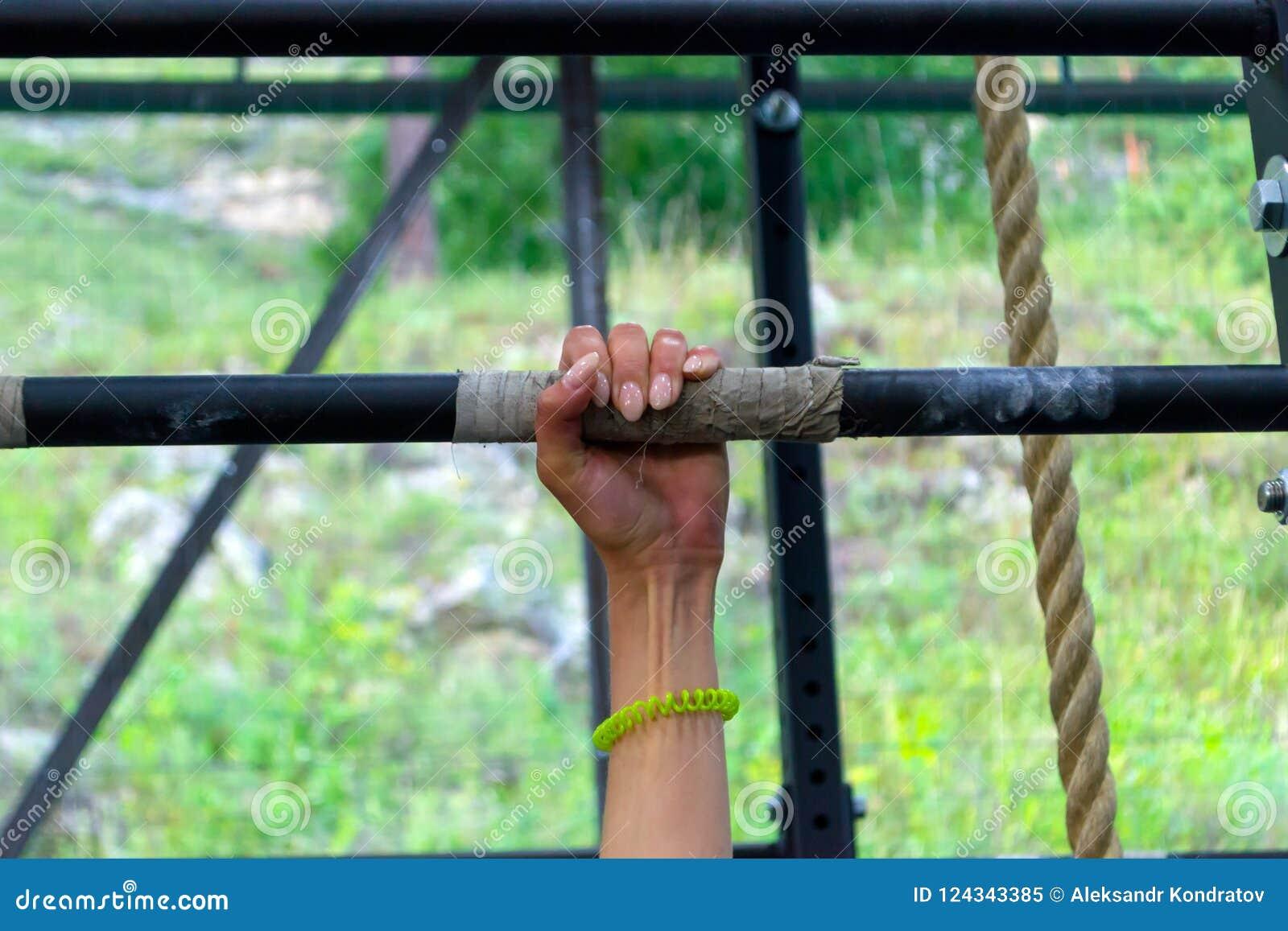Entregue a menina com um tratamento de mãos em uma barra de ferro com veias e a MU tensas