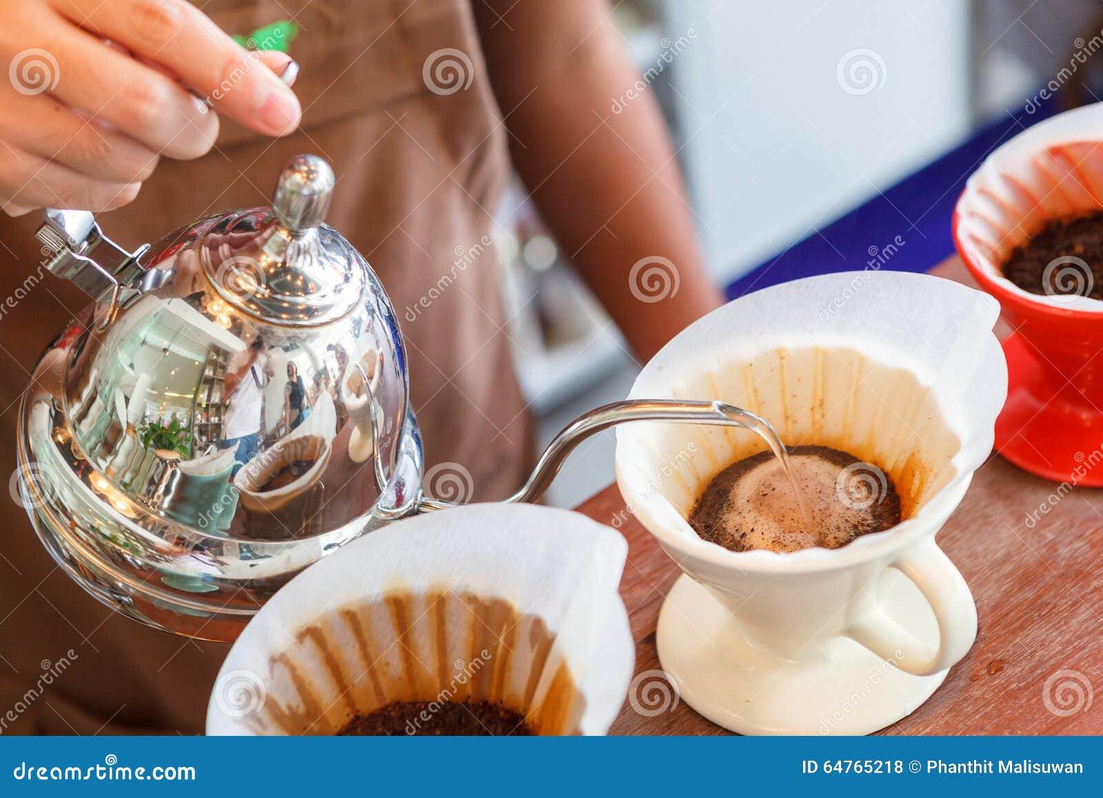Entregue o café do gotejamento, água de derramamento de Barista na borra de café com filtro