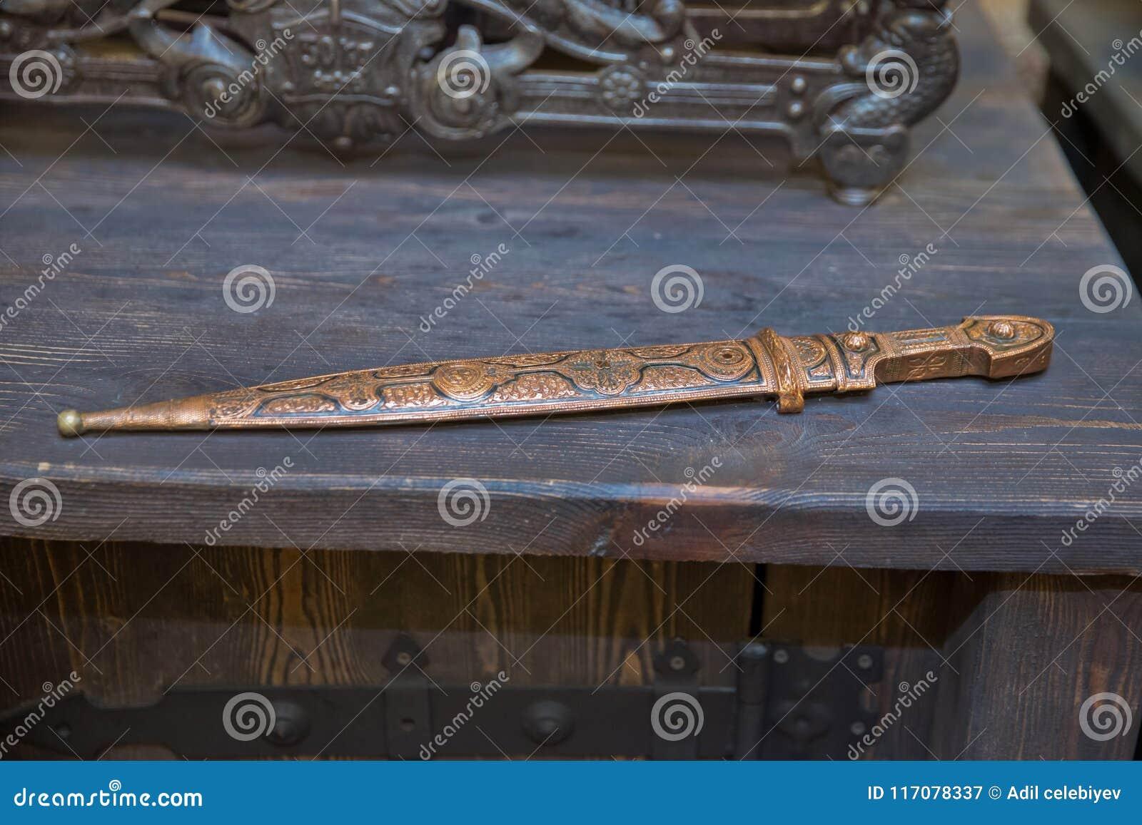 Entregue o cutelo forjado do pirata, uma arma elegante de uma idade mais brutal Espada de cobre em um fundo de madeira