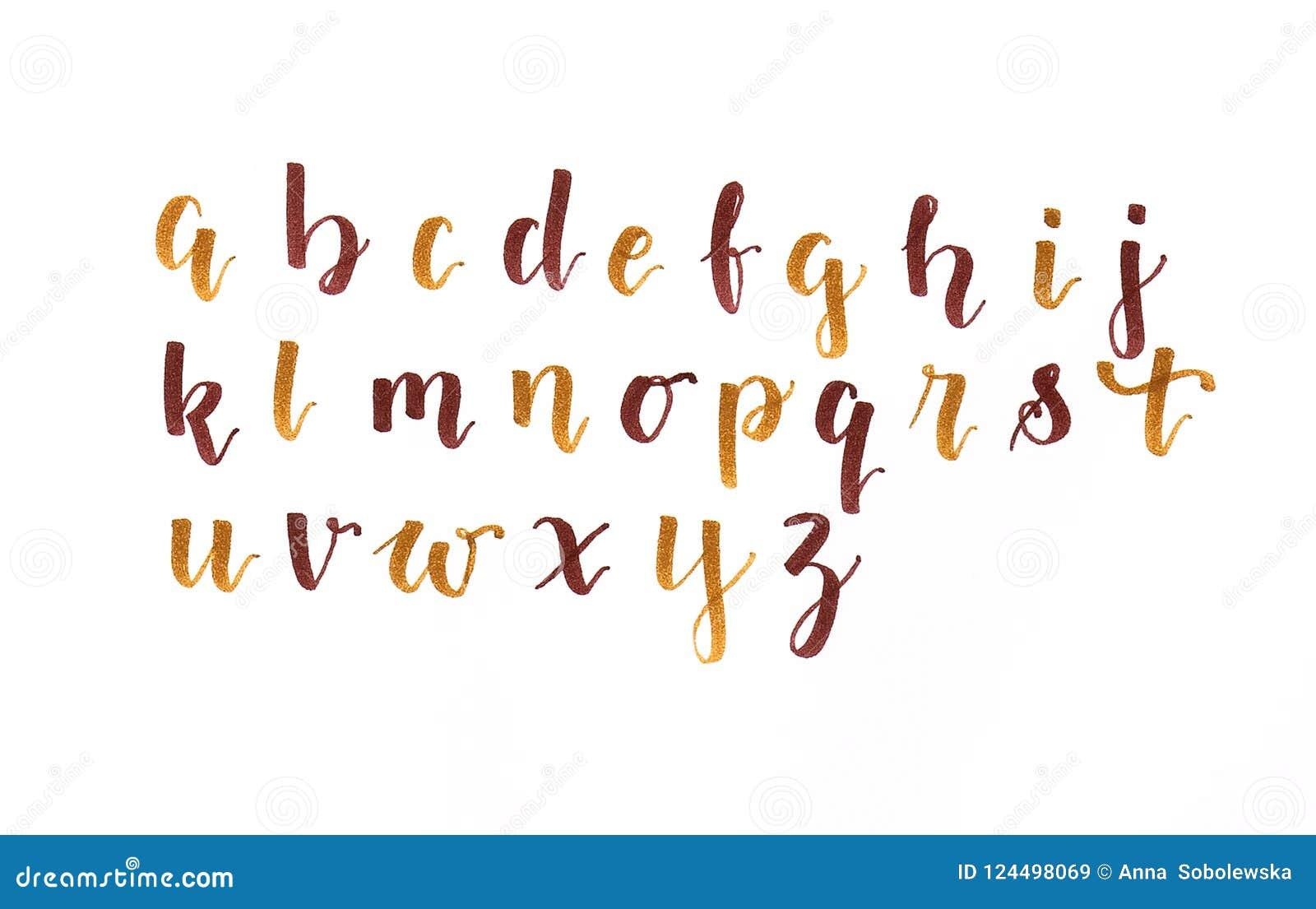 Entregue a rotulação, o alfabeto moderno da caligrafia no marrom outonal das cores e o ouro em um Livro Branco, escrito à mão