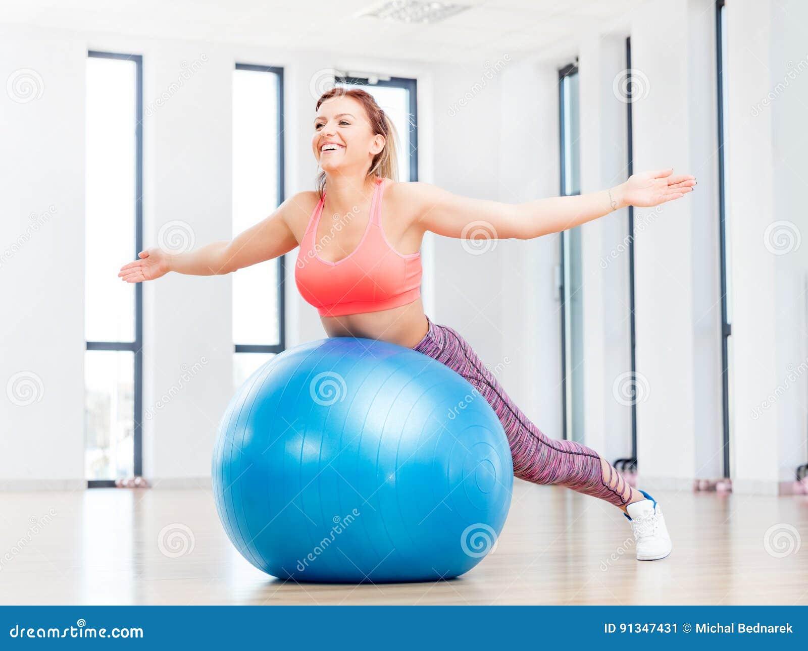 Entrenamiento alegre de la mujer con el fitball en el club de fitness
