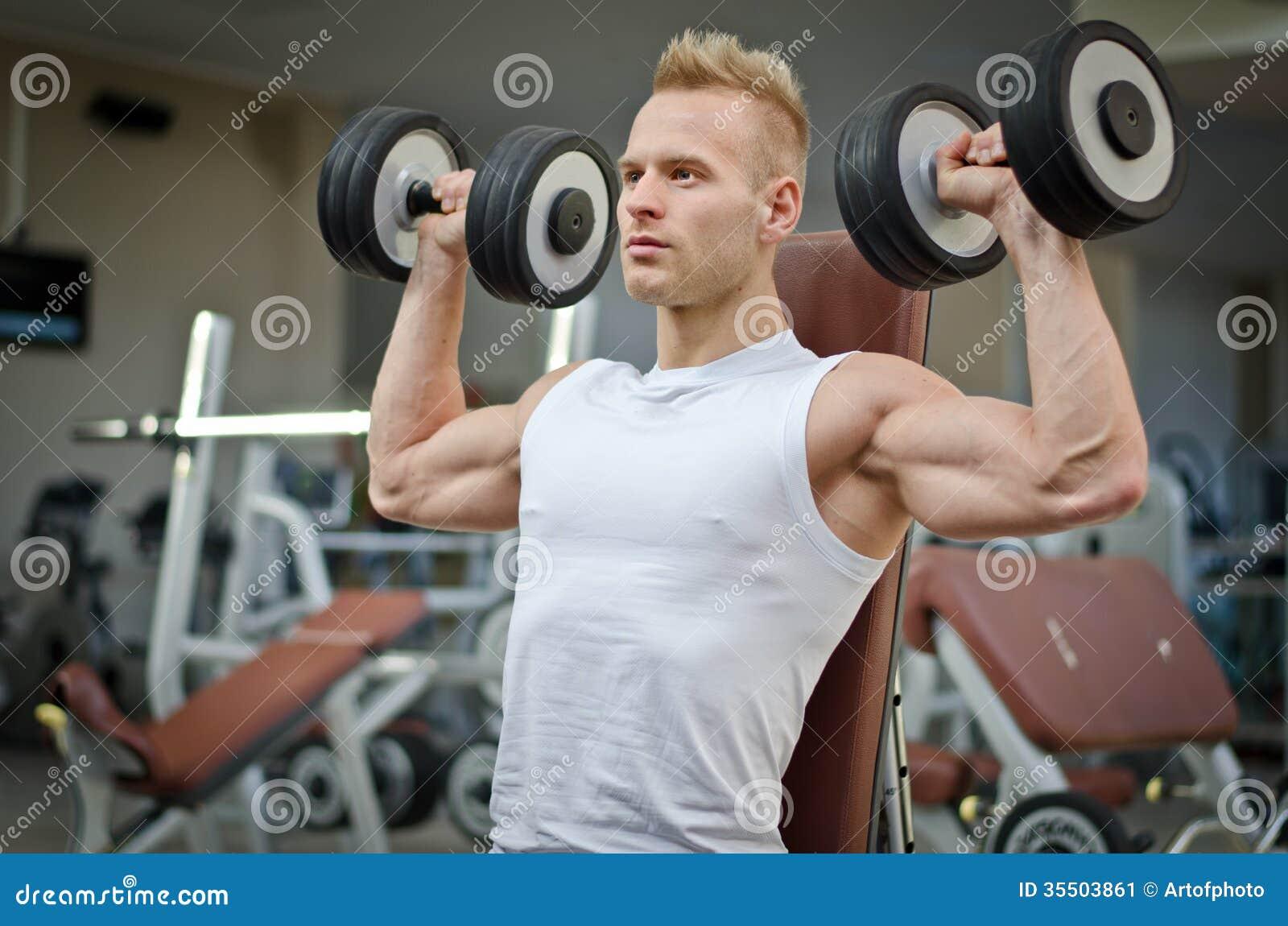 Entrenamiento atractivo del hombre joven con pesas de for Entrenamiento gimnasio