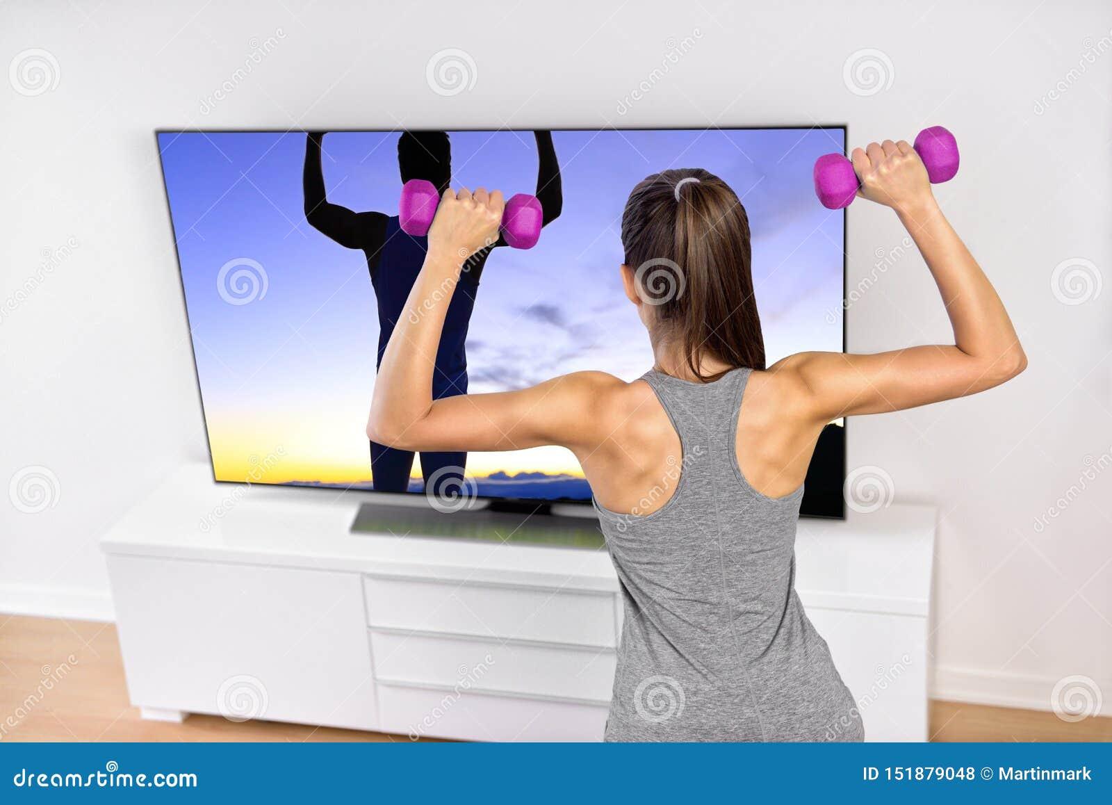 Entrenamiento casero de la fuerza de la mujer de la aptitud que ve la TV