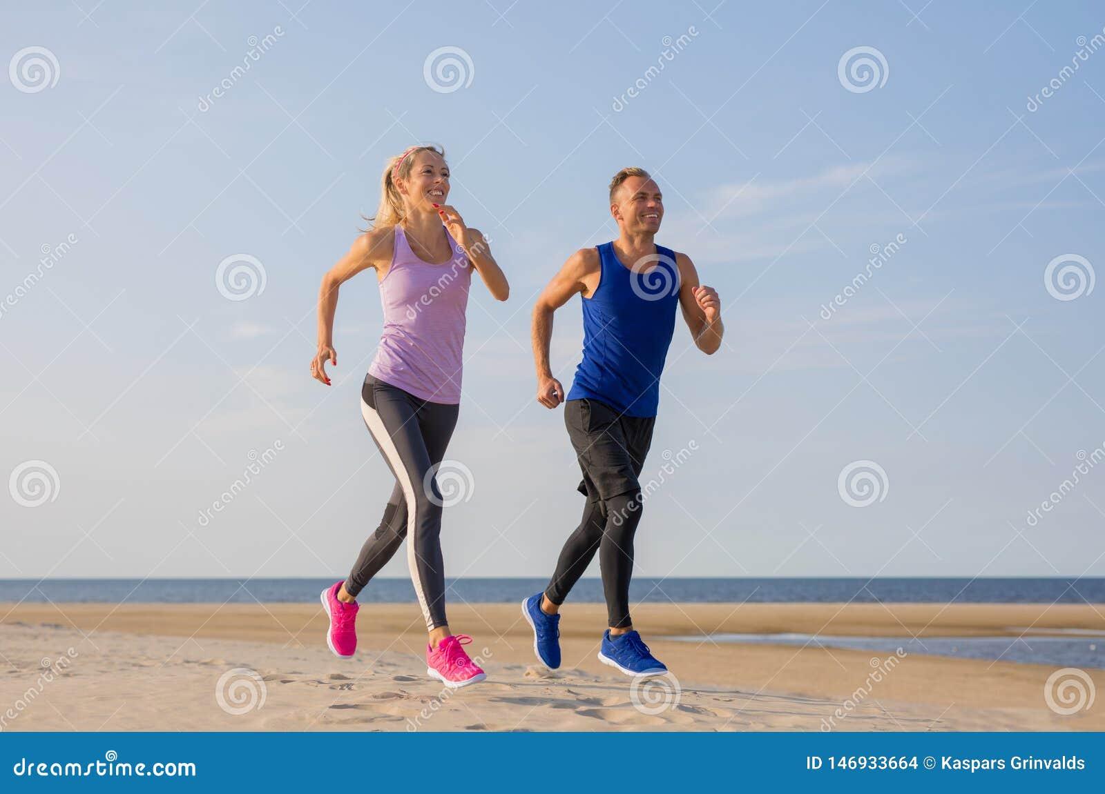 Entrenamiento de funcionamiento de los pares de la aptitud de los corredores en la playa