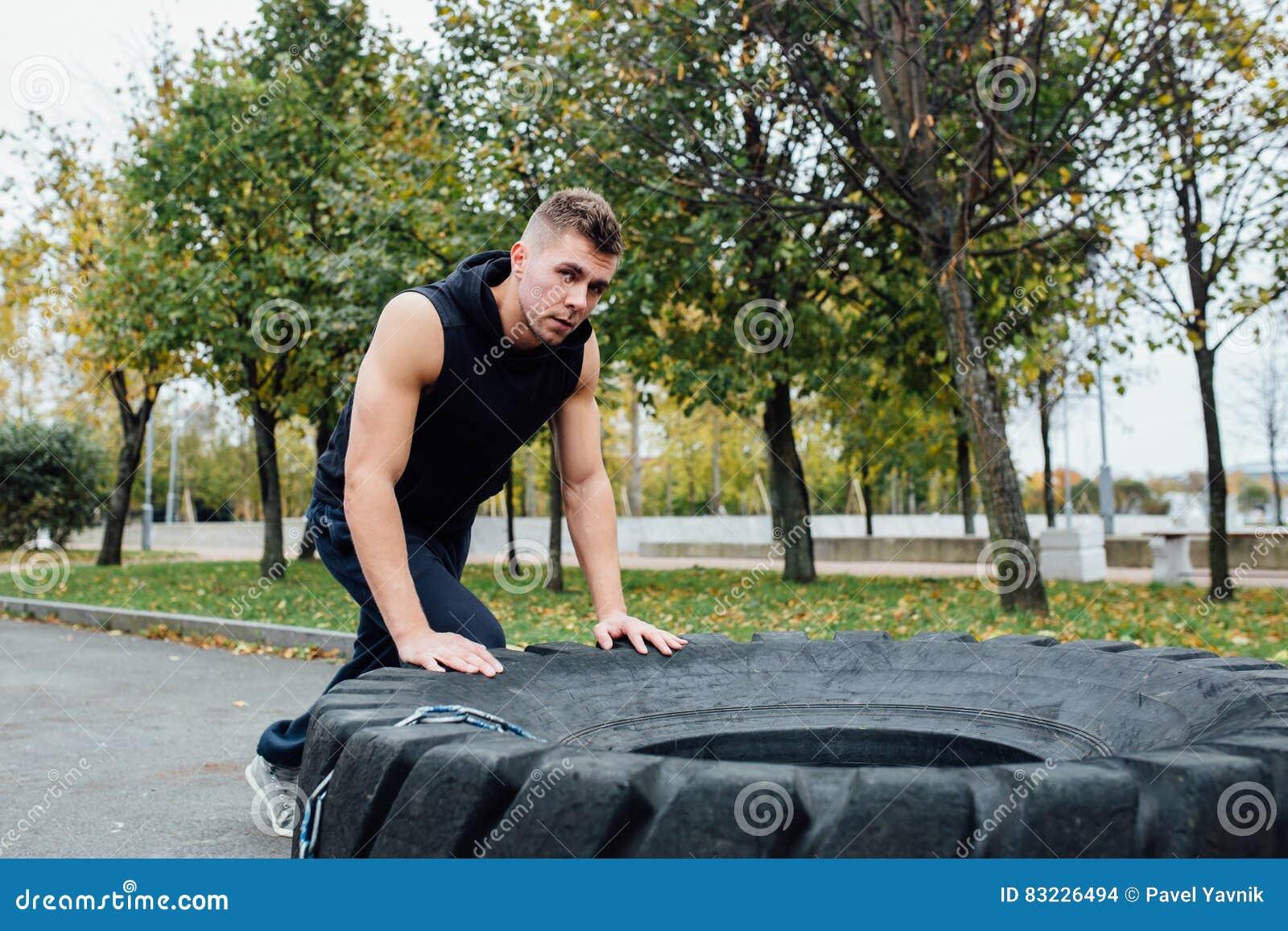 Entrenamiento del hombre del deporte de la aptitud al aire libre con el neumático del tractor