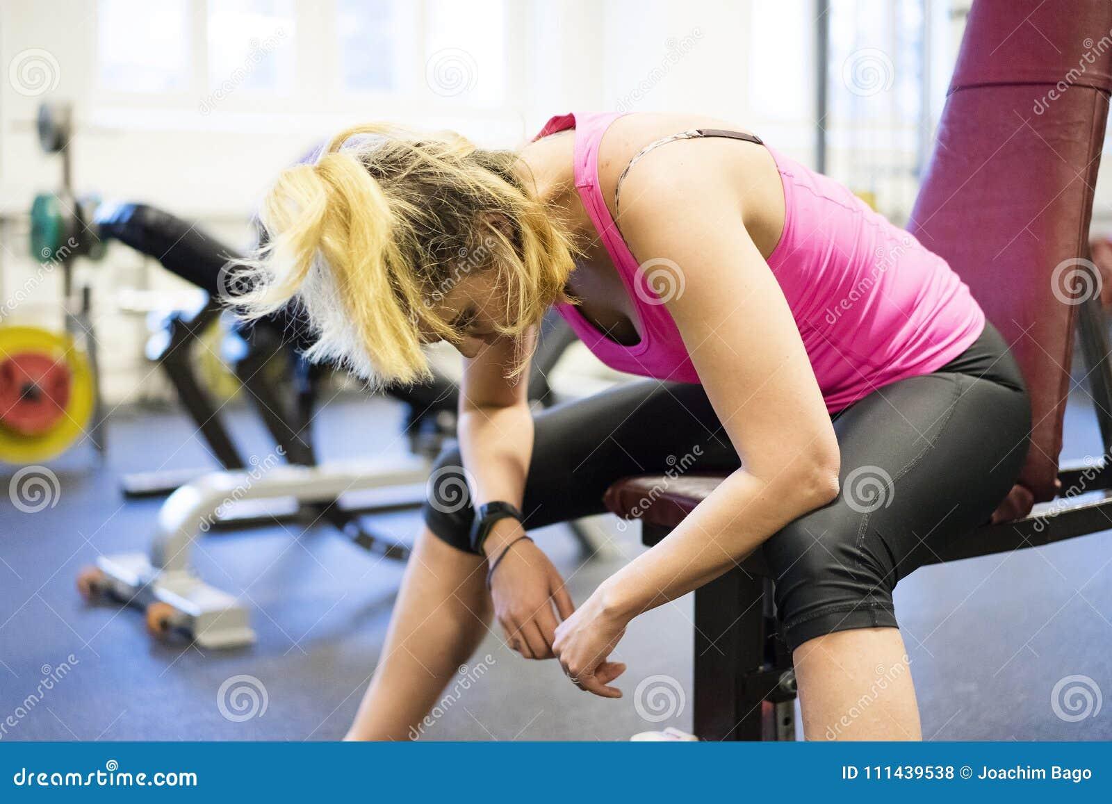 Entrenamiento escandinavo rubio caucásico de la muchacha de la aptitud en la reclinación del gimnasio agotada