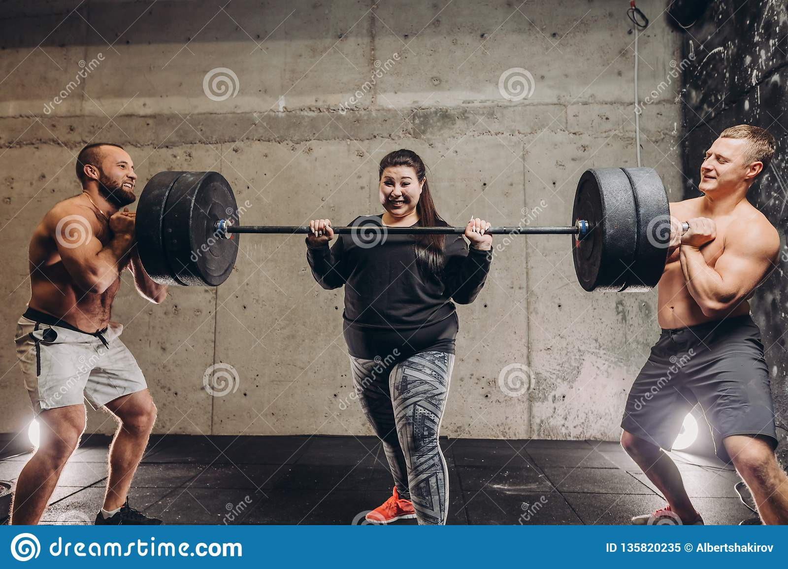 Entrenamiento sudoroso loco gordo de la mujer con los hombres en el gimnasio