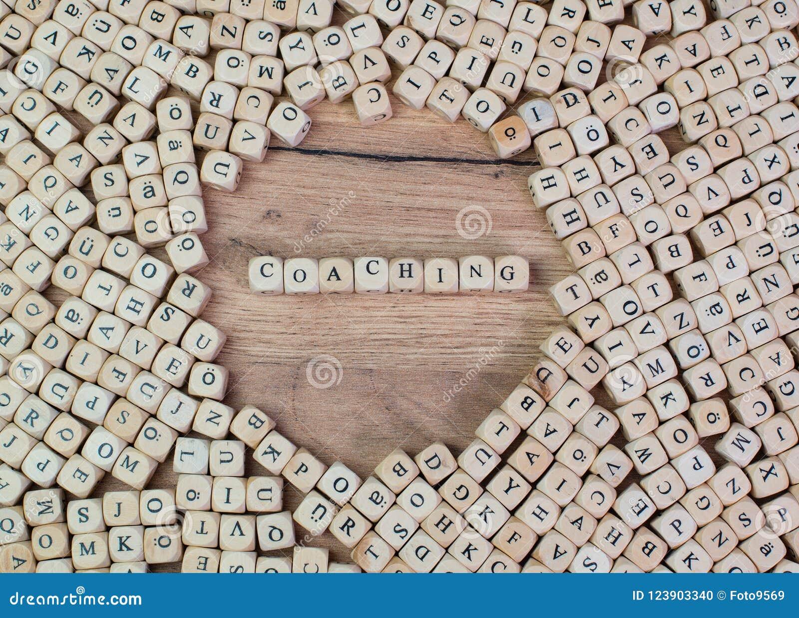 Entrenando, el texto alemán para entrenar, palabra en letras en el cubo corta en cuadritos en la tabla