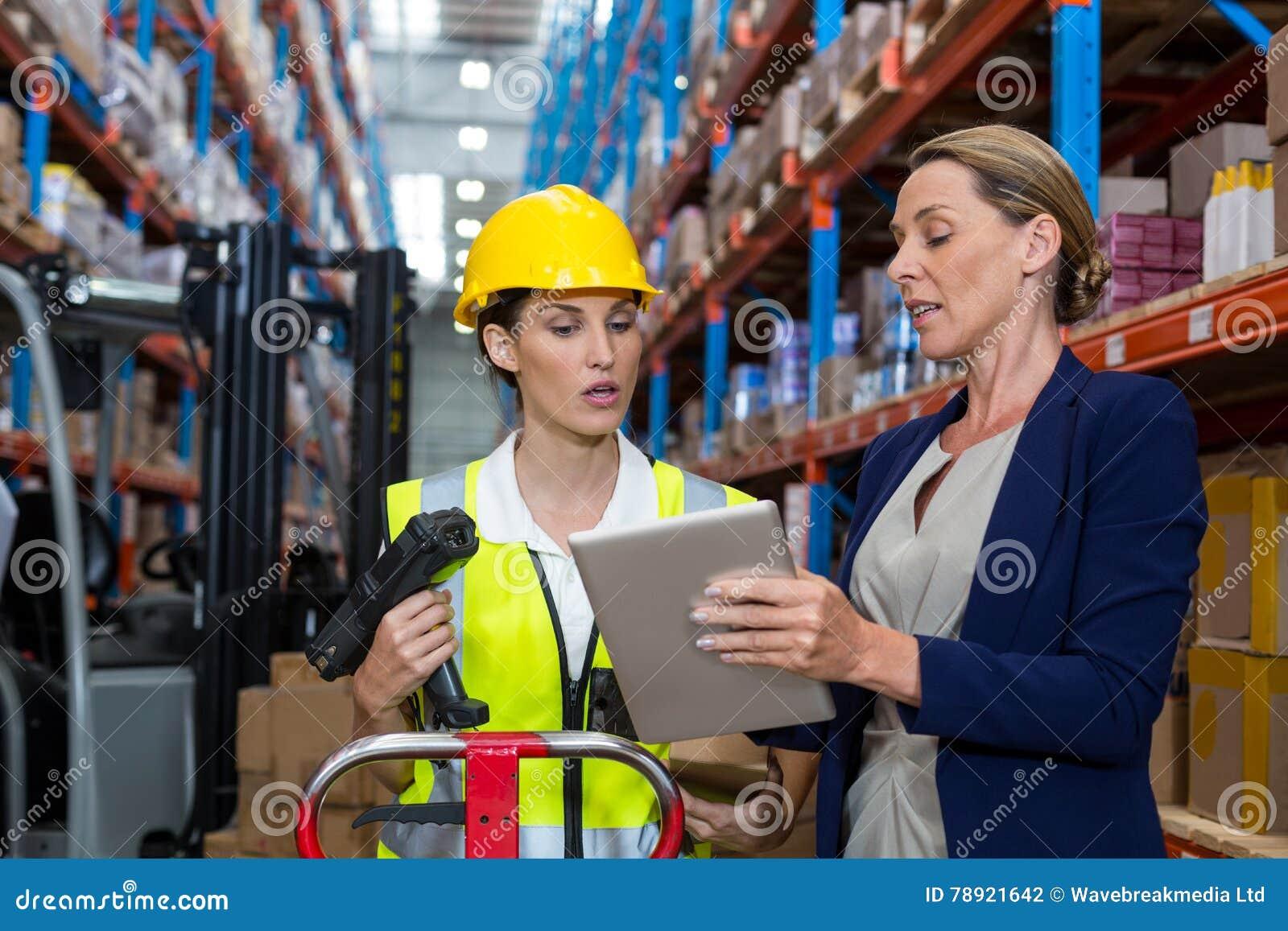 Entreposez le directeur avec le main-d œuvre féminine de interaction au-dessus du comprimé numérique