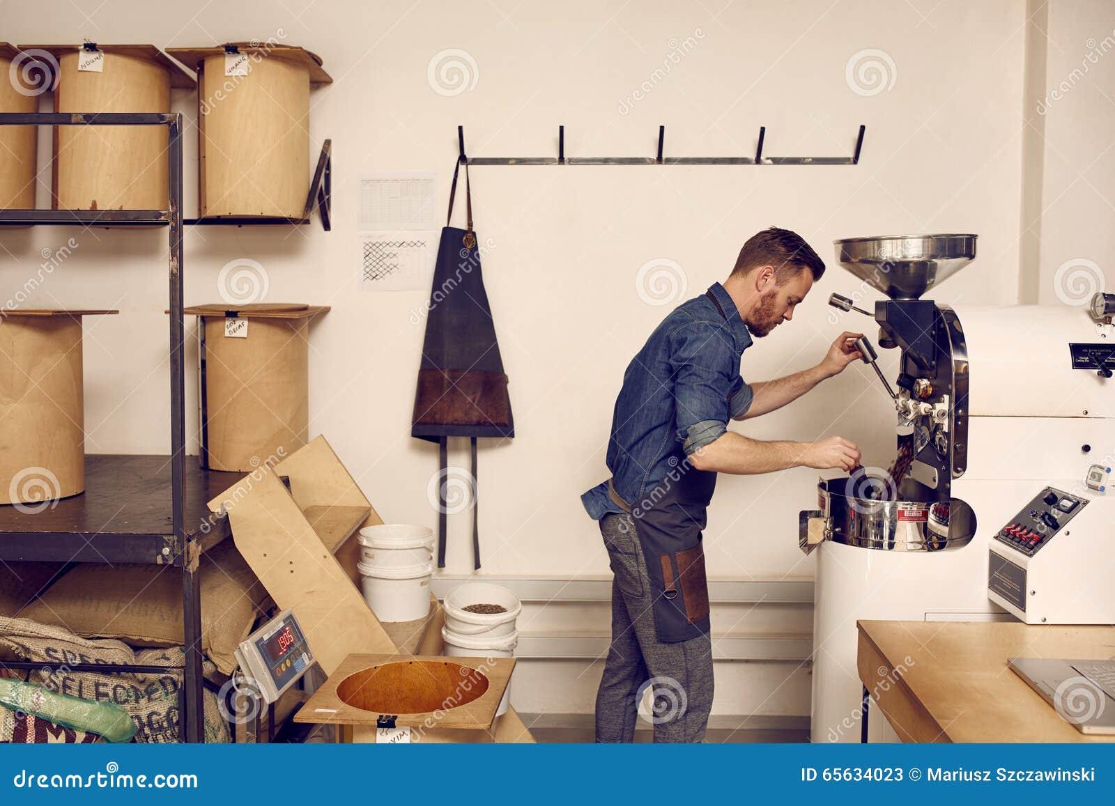 Entrepreneur actionnant une machine moderne de torréfaction de grain de café