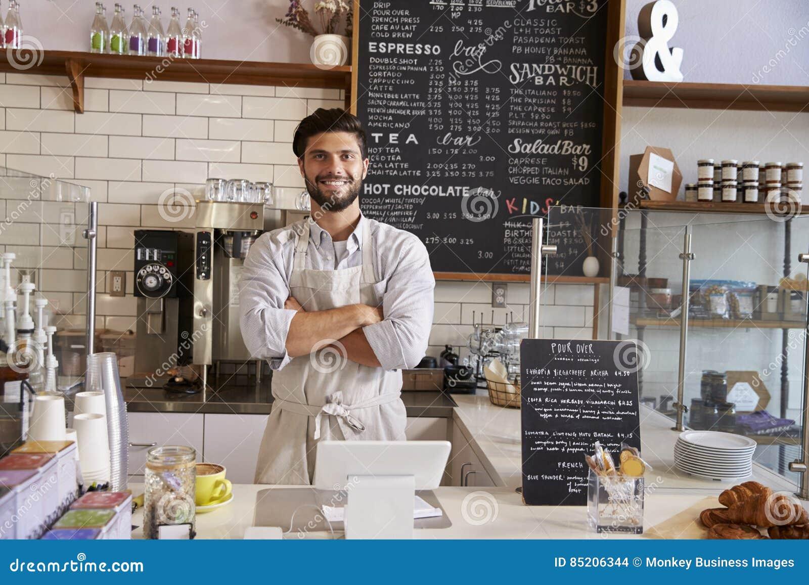 Entrepreneur au compteur du café, bras croisés