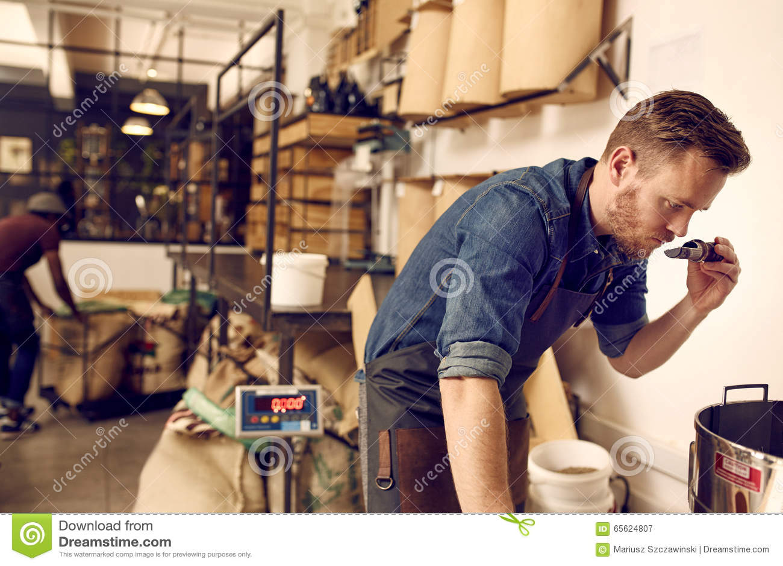 Entrepreneur vérifiant l arome du grain de café fraîchement rôti