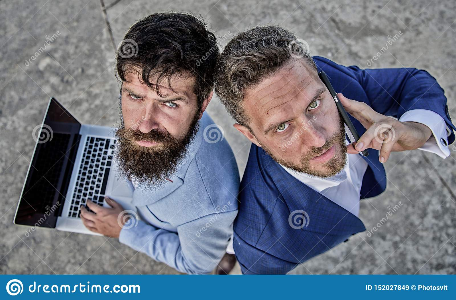 Entrepreneurship as teamwork. Businessmen with laptop and phone call solving problems making deal.