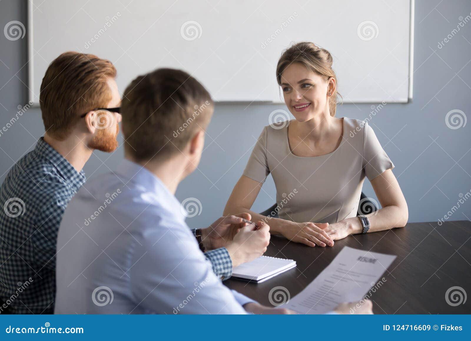 Entrevista femenina sonriente del candidato con los reclutadores masculinos en offic