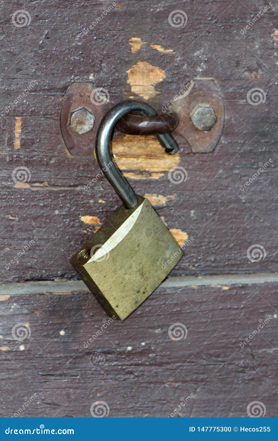 Entriegeltes Vorhängeschloß verließ offen auf dem verrosteten Metall, das mit zwei starken Schrauben an verfallenen hölzernen Bre