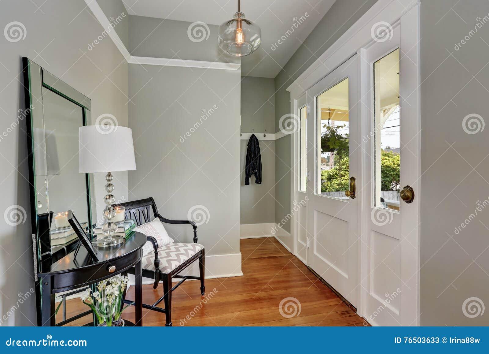 Lichtgrijze Houten Vloer : Entryway met grijze muren consolelijst en houten vloeren stock