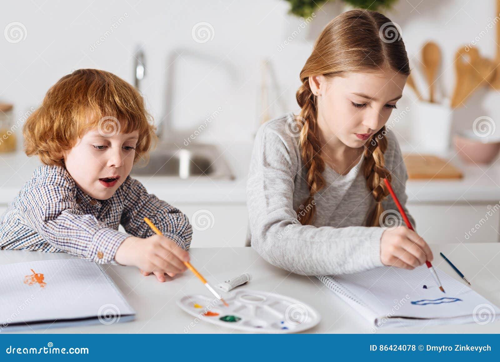 Entschlossene Kreative Geschwister Die In Der Kuche Malen Stockfoto
