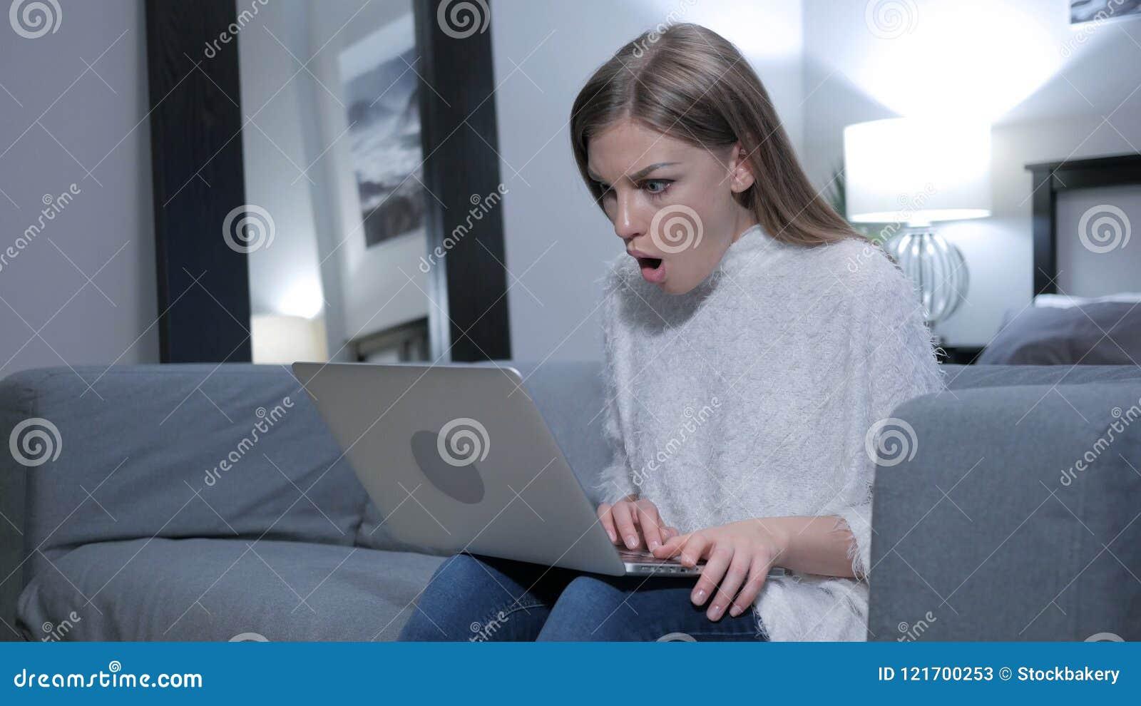 Entsetzte Frau, die den Laptop für Arbeit, wundernd verwendet