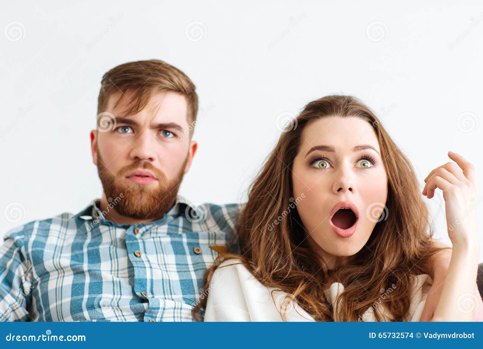 Entsetzte Paare, Die Zu Hause Fernsehen Schauen Stockfoto ...