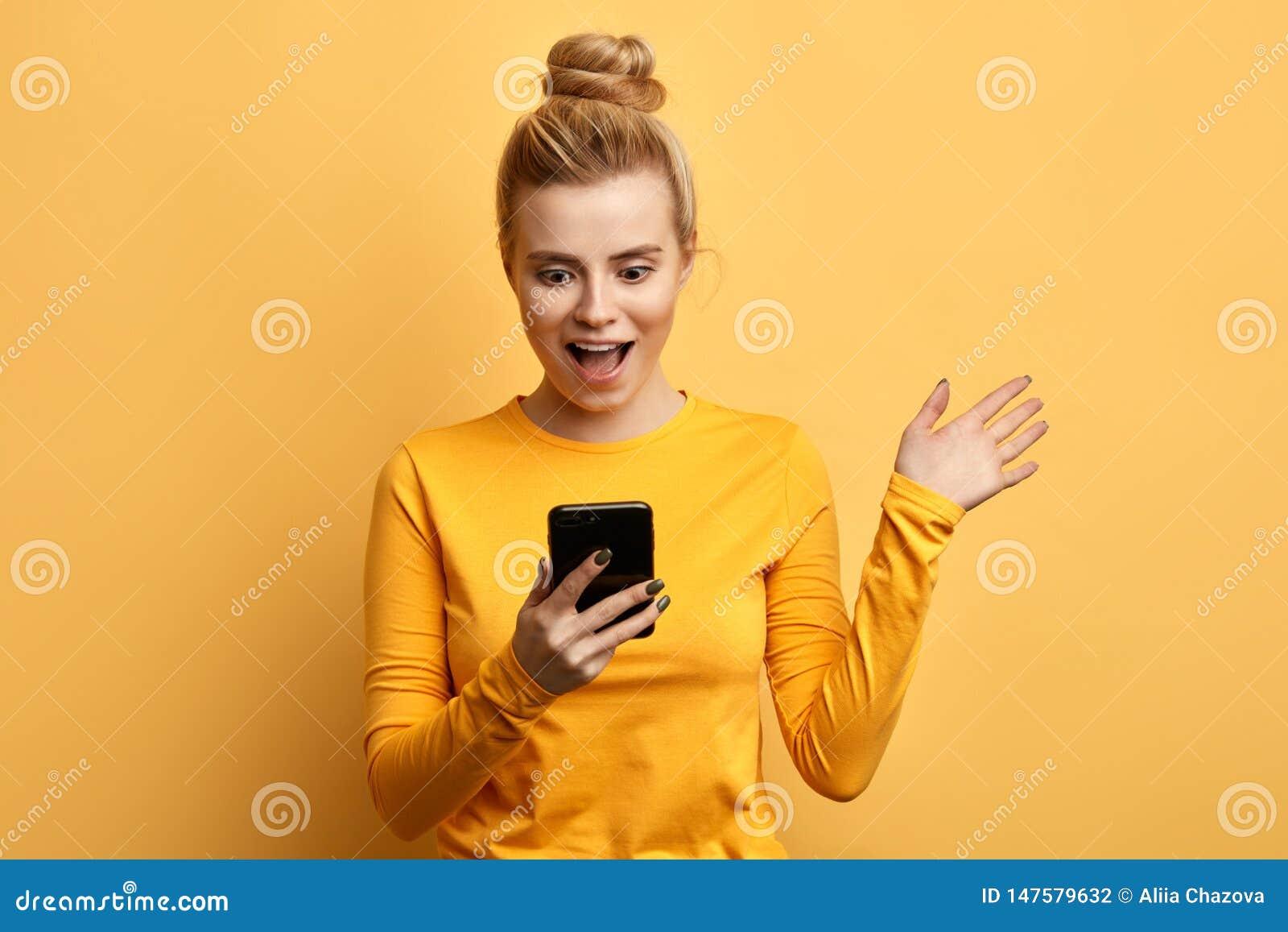 Entsetztes junges emotionales Mädchen, das Handy betrachtet
